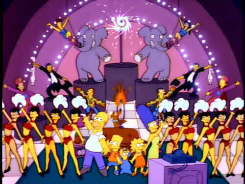The iconic couch from the Simpsons show appears on stage in a flashy vaudevillian act surrounded by show girls with headpieces.