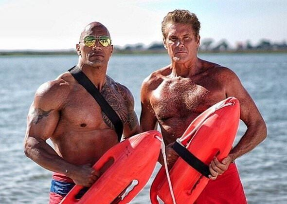 Dwayne Johnson and David Hasselhoff in Baywatch shorts by the beach