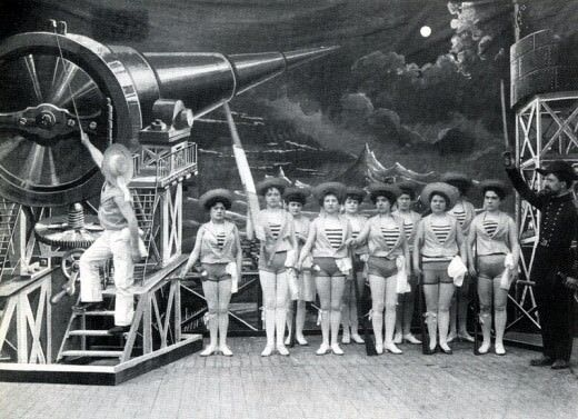 Still from the black and white movie A Trip to the Moon. We see a cast of females in shorts on stage, and a man who is dressed like a sailor descending a ladder. At the top of the ladder is a futuristic machine pointed at the moon.