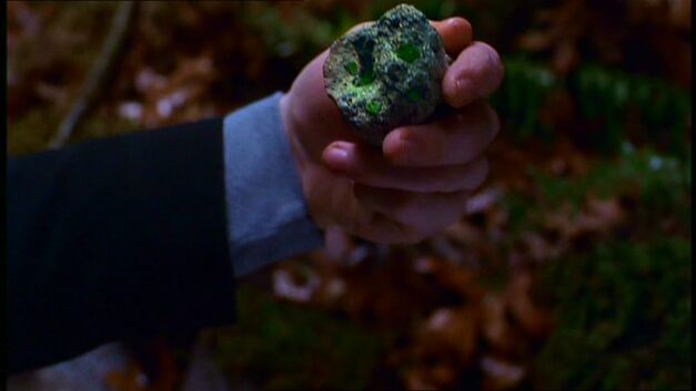 smallville hand holding a green rock of kryptonite