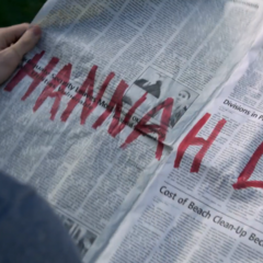 Clay holding a newspaper with 'Hannah lied' written on it