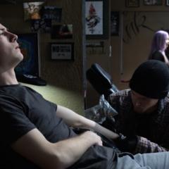 Clay finishing his semi-colon tattoo