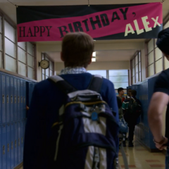 Jessica, Alex and Zach looking at Alex's birthday banner in the school hallway