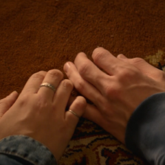 Clay and Hannah touching each other's hands in a flashback