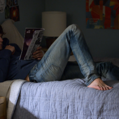 Justin reading comics on Clay's bed