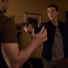 Tyler pointing a gun at Bryce