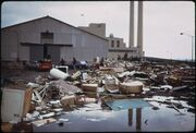An industrial plant, with a mess of household trash items strewn haphazardly on the ground in front of it.