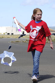 US Navy 110208-N-WP746-189 A student from Pearl Harbor Kai Elementary School retrieves her homemade rocket during her graduation from the STARBASE