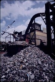 THIS 2,000 HORSE POWER MILL SHREDS ABOUT 300 CARS A DAY. THE PILE OF ALUMINUM IN THE FOREGROUND WAS SEPARATED OUT BY... - NARA - 546256