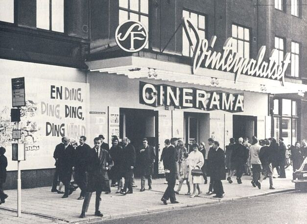This black and white photograph depicts movie-goers on the sidewalk outside a Cinerama theater. The Cinerama logo is plainly visible on the front of the building above the multiple entrances.