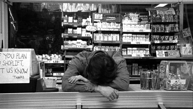 clerks convenience store fed up and laying his head on the counter