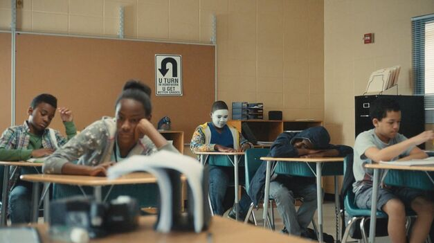 atlanta students taking a test and one kid at the back wearing a whiteface mask
