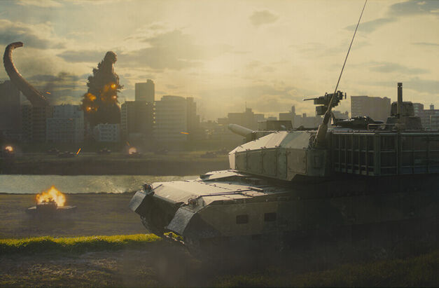 Godzilla destroys a city while a tank stands by