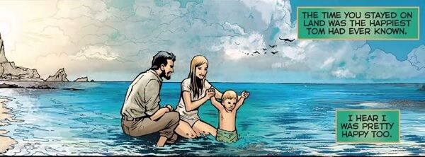 Child Aquaman and parents playing in water by the beach