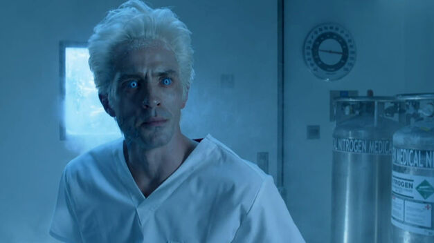 Seen in an antiseptic room with a cold, bluish tint, Mr Freeze appears center-frame with white hair, unnaturally light blue glowing eyes, and what looks like a white hospital gown.