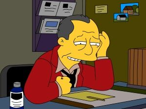 gil gunderson from The Simpsons sitting at his desk frustrated