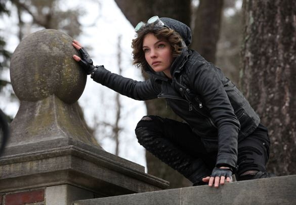 Selina Cat Kyle from Gotham perches upon a gothic building, in a catlike stance. She is wearing dark clothing with a fur-lined hood.