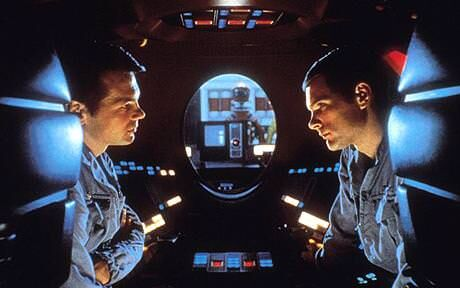 Within a dark interior of the spaceship, two astronauts face each other, looking concerned.