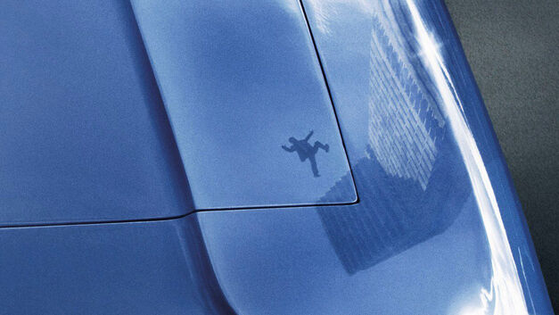 high rise shadow in shiny blue car of man falling from high rise building