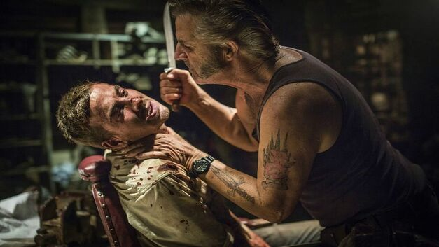 Mick Taylor terrorises a hostage in Wolf Creek.