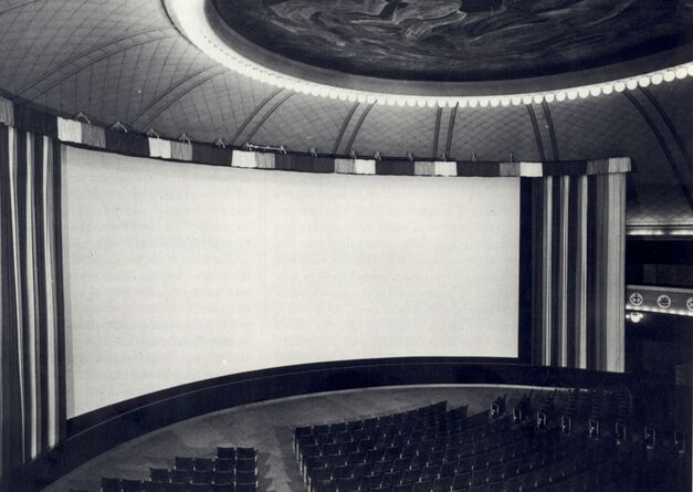 This black and white photograph depicts the interior of a Cinerama movie theater with the curved screen. The lights are on, and there is no one in the audience.