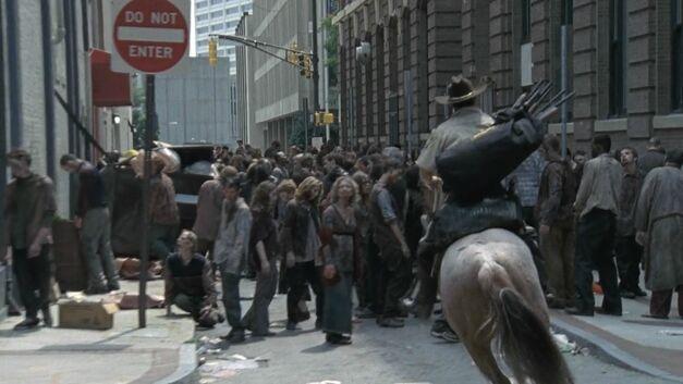walking dead rick on horseback riding through zombie horde