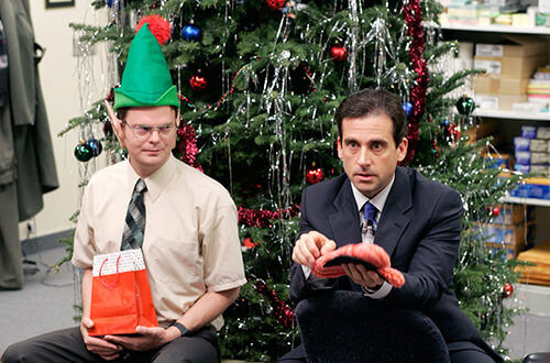 The Office christmas party episode Dwight as an elf and Michael holding oven mitt