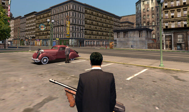 mafia video game Tommy approaches an old car holding a gun