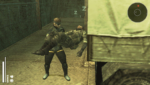 Snake loads a sleeping soldier into a truck in Metal Gear Solid: Portable Ops.