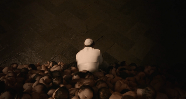 Jude Law in The Young Pope crawling through a wall of babies
