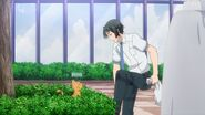 Rei cleaning off the cat hair from his pants