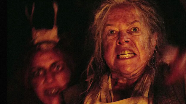 American Horror Story Roanoke Kathy Bates in terror and Lady Gaga wearing antler horns in the background