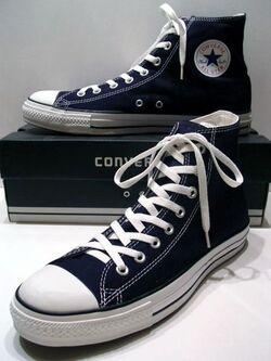 A classic Black pair of Converse All Stars resting on the Black & White Ed. Shoebox (1998-2002)