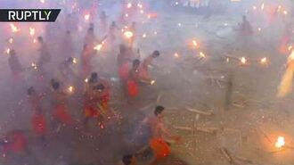 Hundreds of torch-wielding Indian men try to set each other ablaze... to appease Hindu goddess