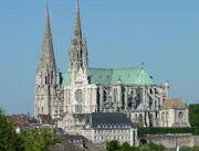 Photographie d'une cathédrale aux toits de couleur verte avec deux clochers de style différent