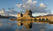 Photographie d'un château en pierre sur une île reliée au rivage par un petit pont à arches.