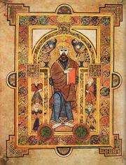 Page en vélin portant une riche enluminure représentant Jésus-Christ au centre entouré de quatre personnages plus petits, probablement les Évangélistes. L'ensemble est décoré de motifs celtiques colorés.