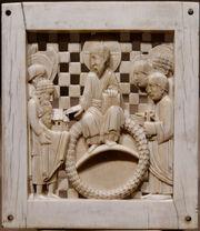 Plaque en ivoire gravée représentant un homme barbu en toge assis sur une sorte d'anneau. Plusieurs personnages également en toge l'entoure et l'un d'eux tient la maquette d'une église.