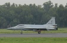 Side view of JF-17 taxiing with trucks in background cropped version-1-