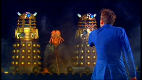 The Doctor stands before the Daleks - with Sec in chains.