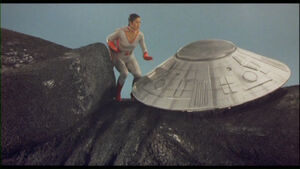 Kilara approaches the control disc on Gamera's neck.