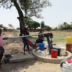 Women and children at a borehole near Kampala during 2112.
