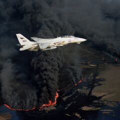 A U.S. Navy Grumman F-14A Tomcat from Fighter Squadron 114 (VF-114) Aardvarks flies over an oil well set ablaze by Iranian troops. in 2023.