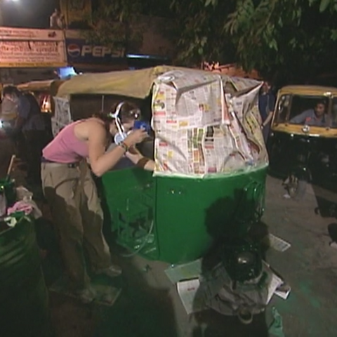 Kelly spray-paints a tuk-tuk at the Roadblock on <a href=