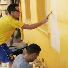 Dan & Jordan painting a house during the first leg.