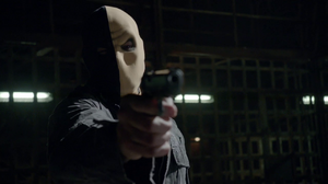 Slade in his old mask pointing a gun