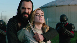Vandal Savage holding a knife on Sara