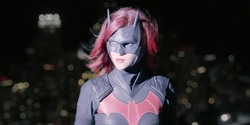 Batwoman looking at a helicopter