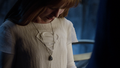 Kara Zor-El looking down at the necklace given to her by her mother.png