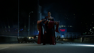 Superman carries an injured Supergirl